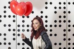 Älskvärd modeflicka med valentinhjärtaballonger Royaltyfria Bilder
