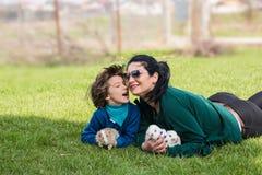 Älskvärd moder och son med bunnys i gräs royaltyfri fotografi