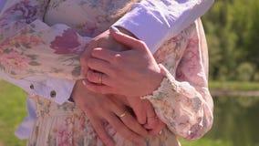 Älskvärd paromfamning på banken av sjön och omfamningen Härligt grabben med flickaställningen i en omfamning på stock video