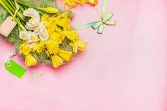 Älskvärd pingstliljagrupp med den tomma etiketten och band på bakgrund för pastellfärgade rosa färger, bästa sikt, ställe för tex Royaltyfri Foto