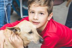 Älskvärd pojke som kramar en hund royaltyfria bilder