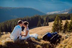 Älskvärd romantisk brud och brudgum som kysser på bergmaximumet Bröllopsresa i fjällängar royaltyfri bild