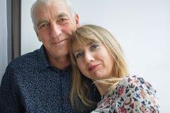 Älskvärd romantisk stående av den äldre mannen som kramar hans unga blondin-haired fru som bär den varma klänningen Par med ?lder royaltyfri fotografi