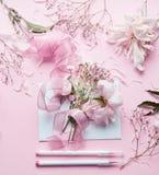 Älskvärd rosa blomsterhandlareworkspace Härliga blommor, packar in, bandet, och markörer ritar på pastellfärgad bakgrund, bästa s Royaltyfri Foto