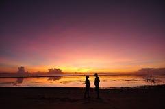 älskvärd soluppgång för balinesestrandpar Arkivfoto
