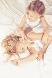 Älskvärd syskongrupp som hemma ligger i säng Royaltyfri Foto