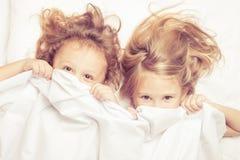Älskvärd syskongrupp som hemma ligger i säng Royaltyfri Fotografi