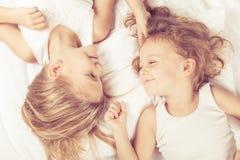Älskvärd syskongrupp som hemma ligger i säng Arkivbild