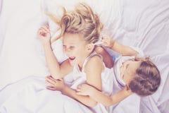 Älskvärd syskongrupp som hemma ligger i säng Royaltyfria Foton