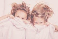 Älskvärd syskongrupp som hemma ligger i säng Fotografering för Bildbyråer