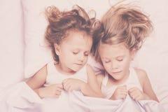 Älskvärd syskongrupp som hemma ligger i säng Arkivbilder