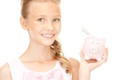 Älskvärd tonårs- flicka med spargrisen och pengar Arkivbilder