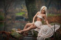Älskvärd ung dam som sitter nära floden i förtrollade trän Den sinnliga blondinen med vit beklär att posera provocatively i höstl Royaltyfria Bilder