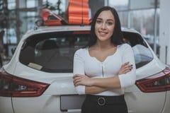 Älskvärd ung kvinna som köper den nya bilen på återförsäljaren royaltyfria bilder