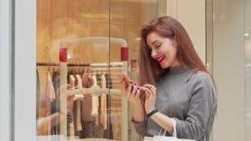 Älskvärd ung kvinna som skrattar, genom att använda den smarta telefonen, medan shoppa på gallerian arkivfilmer