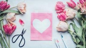 Älskvärd våråtlöje för pastellfärgad färg upp med tulpan, saxen, markörer och rosa färger packar den pappers- påsen med hjärta Royaltyfria Bilder
