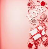 Älskvärd valentindagbakgrund med ordförälskelse, gåvaasken, hjärtor och garnering, bästa sikt royaltyfri fotografi