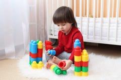 Älskvärda 2 år litet barn som spelar plast- kvarter Fotografering för Bildbyråer