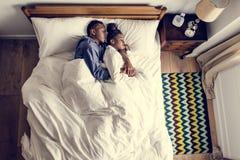 Älskvärda afrikansk amerikanpar som smyga sig i säng royaltyfri foto