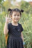 Älskvärda asiatiska barn som bär skolaryggsäcken, räcker undertecknande nolla K Royaltyfri Bild