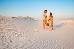 Älskvärda attraktiva par på den vita sandstranden eller i öknen eller i sanddyerna, grabb och en flicka med en korg i deras hand arkivfoto