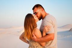 Älskvärda attraktiva par som kysser på den vita sandstranden eller i öknen eller i sanddyerna, lyckliga par som omfamnar på beace Arkivfoton