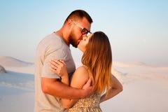 Älskvärda attraktiva par som kysser på den vita sandstranden eller i öknen eller i sanddyerna, lyckliga par som omfamnar på beace Royaltyfri Bild