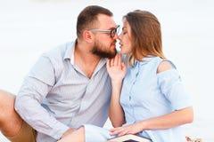 Älskvärda attraktiva par som tillsammans sitter på den vita sandstranden som ser sig, barn kopplar ihop att kyssa på stranden, fö Arkivfoton