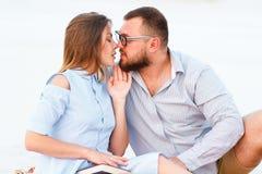 Älskvärda attraktiva par som tillsammans sitter på den vita sandstranden som ser sig, barn kopplar ihop att kyssa på stranden, fö Fotografering för Bildbyråer