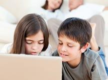 Älskvärda barn som håller ögonen på en film på deras bärbar dator 库存照片