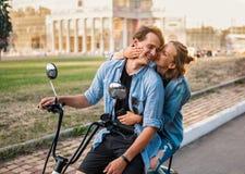 Älskvärda barnpar som kör den elektriska cykeln under sommar fotografering för bildbyråer