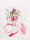 Älskvärda blommor samlar ihop och förbigår hälsningkortet med det rosa bandet och skriver eller markören på vit träbakgrund royaltyfria foton