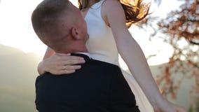 Älskvärda brölloppar i solnedgång Brudgummen rotera bruden på hans hand lager videofilmer