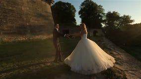 Älskvärda brölloppar som kysser slappt i den härliga solnedgången för skog på bakgrund Charmigt ögonblick stock video