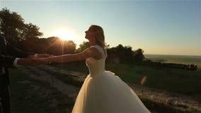Älskvärda brölloppar som kysser slappt i den härliga solnedgången för skog på bakgrund Charmigt ögonblick lager videofilmer