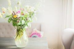 Älskvärda lösa blommor samlar ihop i den glass vasen på tabellen i ljus vardagsrum, hem- garnering arkivfoton