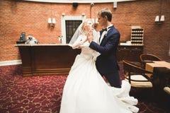 Älskvärda lyckliga brölloppar, brud med den långa vita klänningen som poserar i härlig stad Royaltyfri Bild