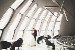 Älskvärda lyckliga brölloppar, brud med den långa vita klänningen som poserar i härlig stad royaltyfria foton