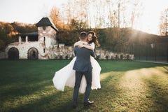 Älskvärda lyckliga brölloppar, brud med den långa vita klänningen som poserar i härlig stad royaltyfri fotografi