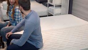 Älskvärda lyckliga par som ligger på den bekväma othopedic madrassen på möblemang, shoppar arkivfilmer