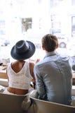 Älskvärda par från baksida som ser på gatan i kafé arkivfoto
