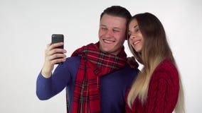 Älskvärda par i varma hemtrevliga kläder som tar selfies som använder tillsammans den smarta telefonen royaltyfria foton