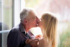 Älskvärda par med det kyssande near öppnade fönstret för ålderskillnad inom huset under sommar Tid Royaltyfria Bilder