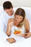 Älskvärda par som äter en fruktsallad royaltyfria foton