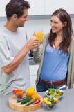 Älskvärda par som klirrar exponeringsglas av orange fruktsaft Arkivfoto