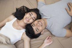 Älskvärda par som ler i säng Arkivfoto