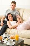Älskvärda par som ligger på soffan i pyjamas Arkivfoton