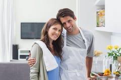 Älskvärda par som omfamnar i kök Arkivbilder