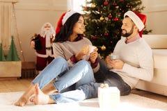 Älskvärda par som talar, medan dricka kaffe på jul Royaltyfri Foto