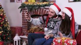 Älskvärda par som talar vid mobil video pratstund och visar gåvor för glad jul lager videofilmer